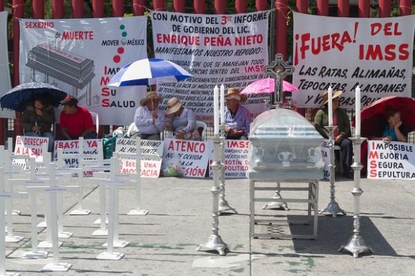 MÉXICO, D.F., 01SEPTIEMBRE2015.- Integrantes de la Asociación de Derechohabientes y Pensionados del Estado de Guanajuato del IMSS, se manifestraon con mantas, cruces de madera y un ataud a las afueras de la Cámara de Diputados, donde en unas horas se entregara el informe presidencial. Los inconformes exigieron a los legisladores no permitan la privatización del IMSS y que las clinicas de la entidad cuenten con las medicinas e instrumentos necesario para atender a los derechoabientes. FOTO: SAÚL LÓPEZ /CUARTOSCURO.COM