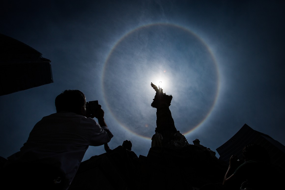 MEXICO CITY, MEXICO - MAY 21: A man takes a photo of the Solar Halo at the Angel de la Independencia, which took place in Mexico City on Thursday. A solar halo occurs when the light is refracted in ice crystals suspended in the atmosphere, on May 21, 2015 in Mexico City, Mexico. (Photo by Manuel Velasquez/LatinContent/Getty Images)